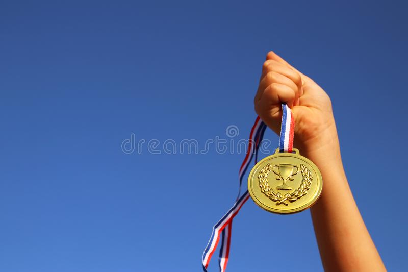 Child hand raised, holding gold medal against sky. education, success, achievement, award and victory concept. stock photography