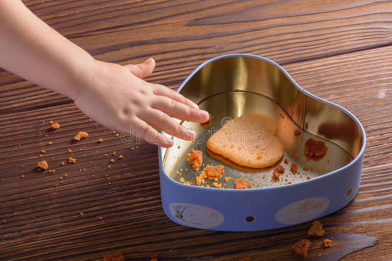 Child hand reaching for last ginger cookie in heart shaped box stock photo