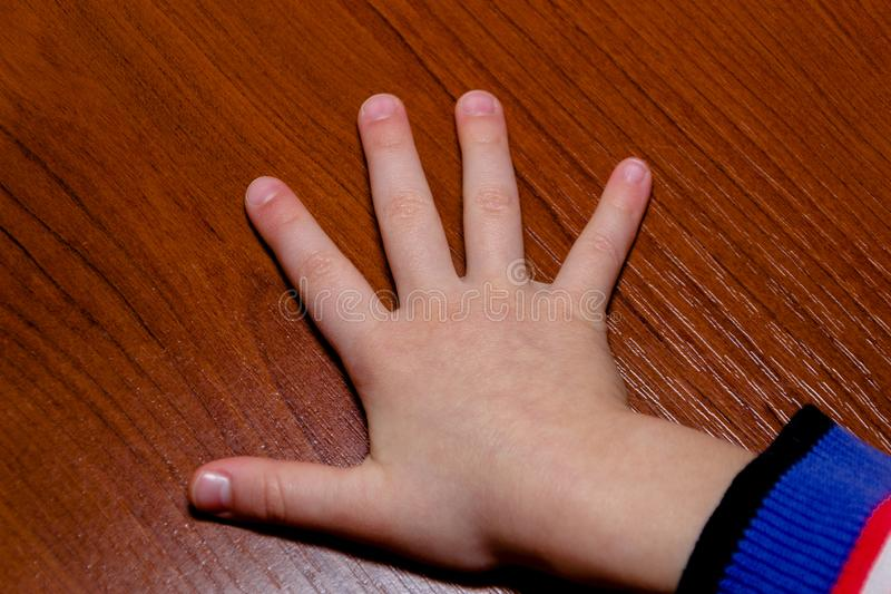 Child hand showing the five fingers isolated on a wood background. Girl royalty free stock image