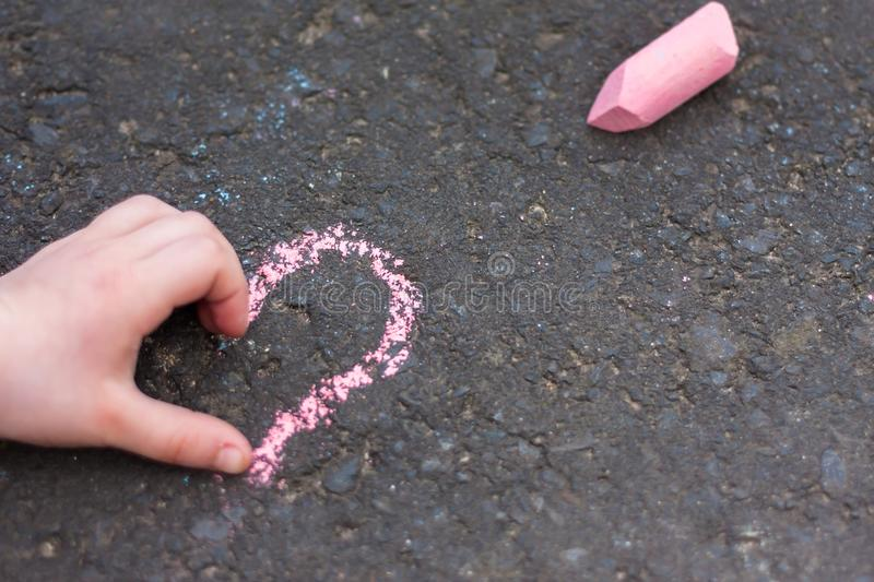 Schoolgirls hand shows heart gesture. Child hand shows heart sign on chalk drawing stock images