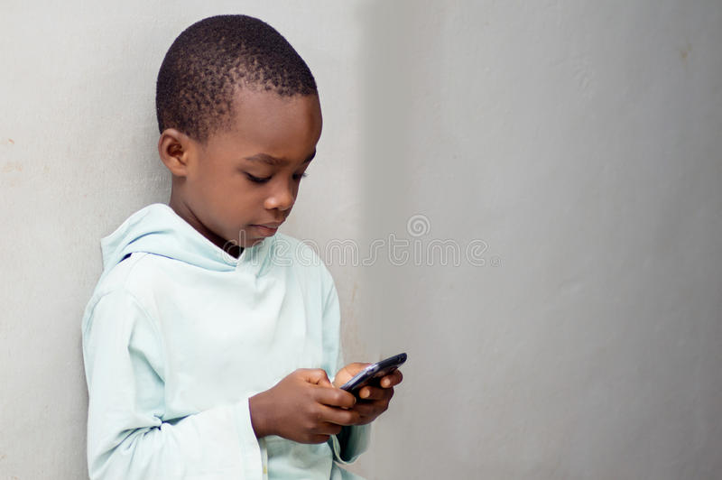 Child handling a cell phone. stock photography