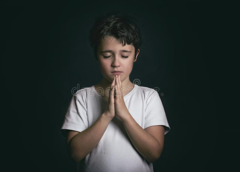 Child with hands clasped together praying royalty free stock image