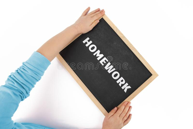 Child hands holding blackboard with text Homework. royalty free stock photography
