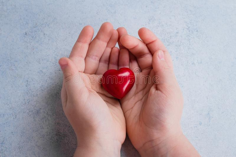 Child hands holding red heart. Card for Valentines day. World heart day, world health day, healthcare, donate and family insurance stock photo