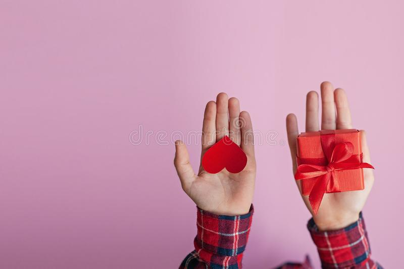 Child hands holding red paper heart and box present in hands on pink background. Valentines day concept. Child hands holding red paper heart and box present in royalty free stock image