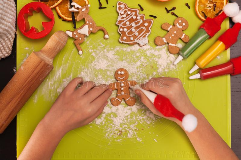 Child hands making gingerbread cookie people - top view royalty free stock image