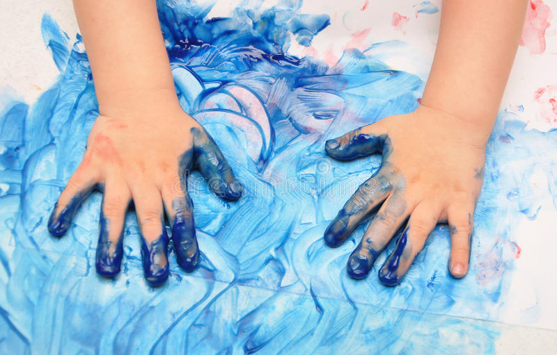 Child hands painted in blue paint royalty free stock image