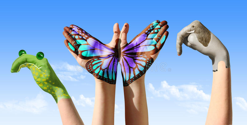 Child hands painted in colorful paints or tattoo with frog, butterfly, elephant.  royalty free stock image