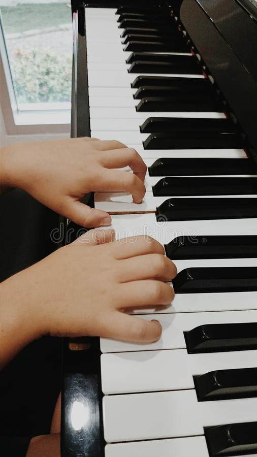 Child hands on piano keys royalty free stock image