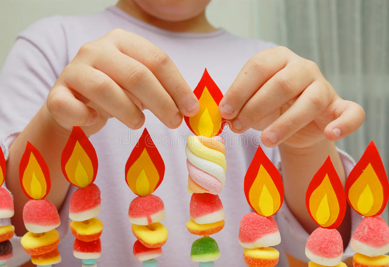 Child hands putting a paper flame on handmade hanukah stock photography