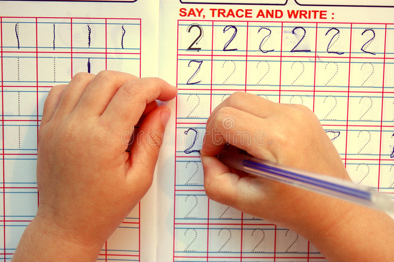 Child hands writing. White little hands of a caucasian toddler child learning by saying, tracing and writing down numbers with a blue pen in a book at preprimary stock photography