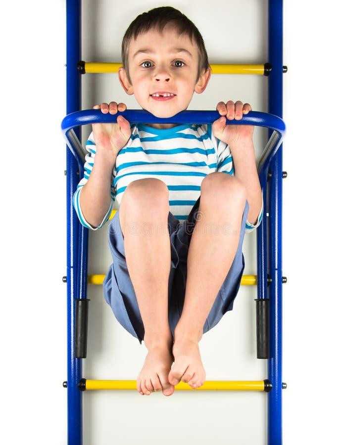 Child hanging on a horizontal bar stock photo