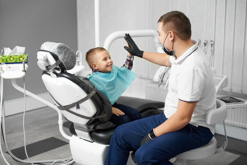A child is happy after dental treatment and giving high-five to his doctor in a modern white dental clinic stock photo