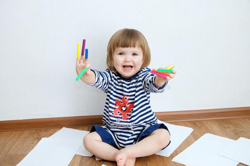 Child happy smiling sitting on floor playing with felt tip pens. baby girl painting and playing. colorful stuff felt pen caps. On fingers of kid royalty free stock image