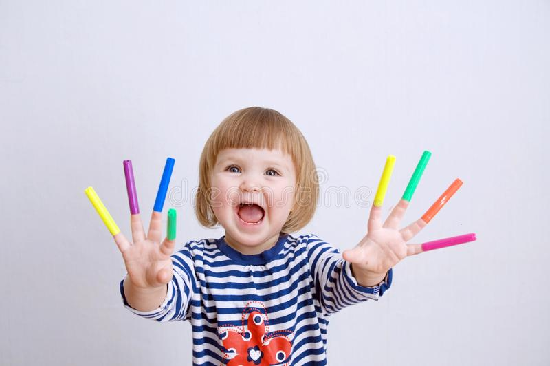 Child happy smiling sitting on floor playing with felt tip pens. baby girl painting and playing. colorful stuff felt pen caps. On fingers of kid stock images