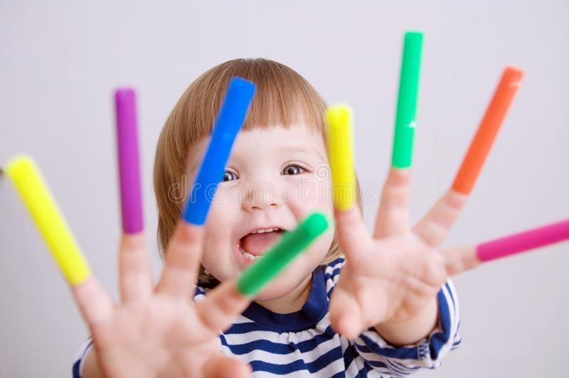 Child happy smiling sitting on floor playing with felt tip pens. baby girl painting and playing. colorful stuff felt pen caps. On fingers of kid stock photography