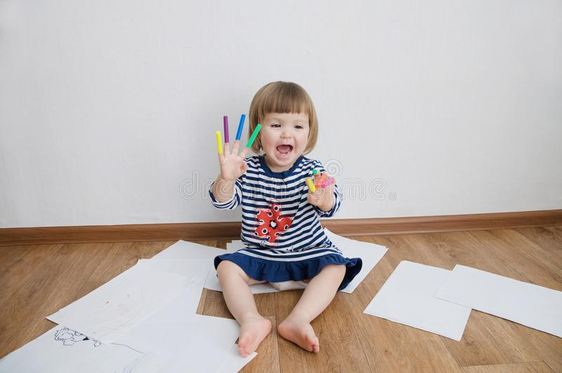 Child happy smiling sitting on floor playing with felt tip pens. baby girl painting and playing. colorful felt pen caps on fingers. Of kid royalty free stock photos
