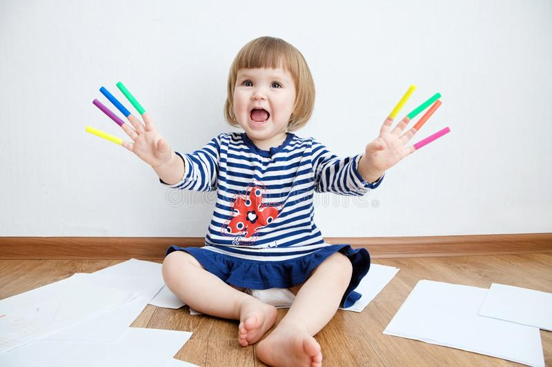 Child happy smiling sitting on floor playing with felt tip pens. baby girl painting and playing. colorful stuff felt pen caps. On fingers of kid royalty free stock photo