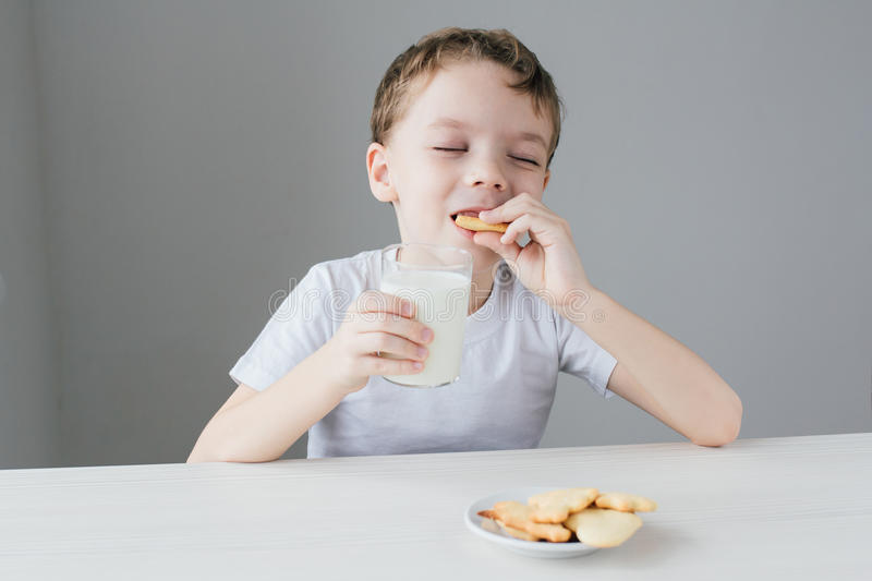 The child is happy to eat homemade biscuits with milk stock photos