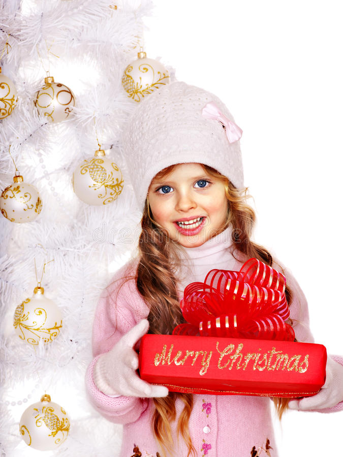 Child in hat and mittens holding red gift box near white Christmas tree. royalty free stock photography
