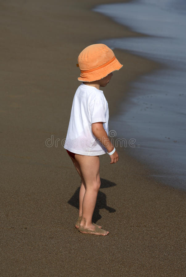 Download Child In Hat Standing On The Beach Stock Photo - Image: 14947230