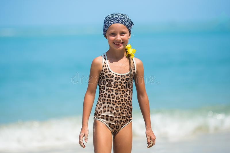 Child having fun at the beach, Cute girl playful in the sunny day, tropical beach.Playing with the sand and waves sea.  royalty free stock images