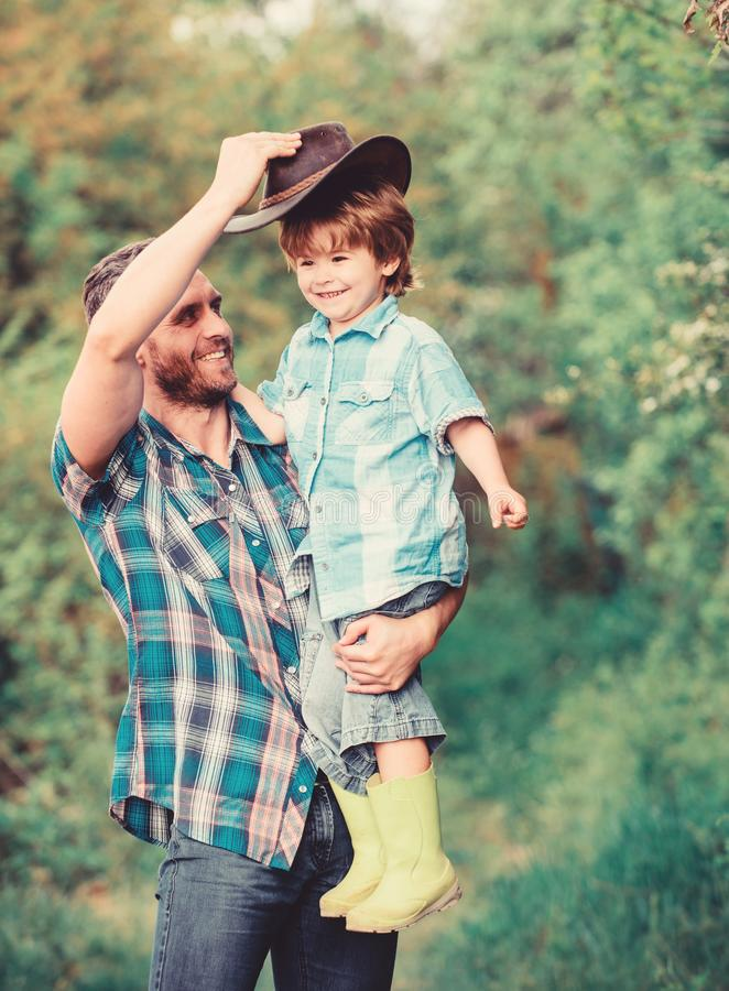Child having fun cowboy dad. Farm family. Holidays at parents farm. Growing cute cowboy. Weekend at farm. Little boy and royalty free stock image