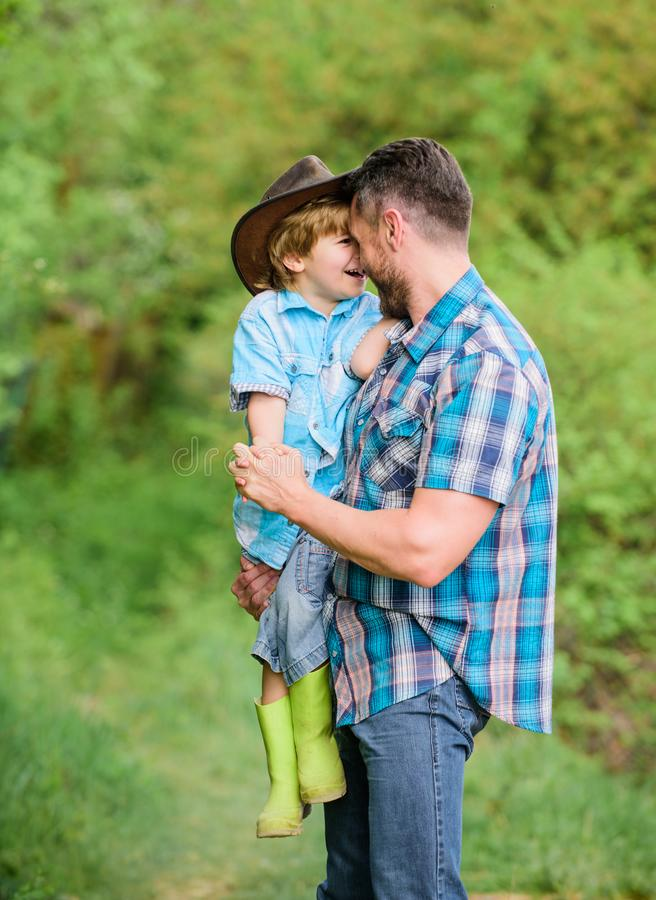 Child having fun cowboy dad. Farm family. Holidays at parents farm. Growing cute cowboy. Weekend at farm. Little helper royalty free stock photo