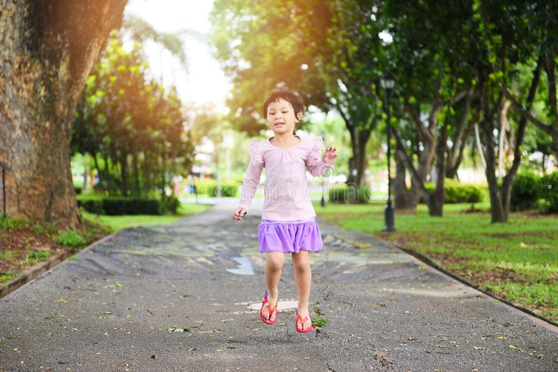 Child having fun playing outside Asian kid girl happy jumping in the park garden tree background - International Children's Day royalty free stock photography