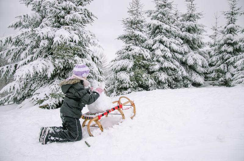 Child having happy winter time with lot of snow and little snowman built in sleight stock images