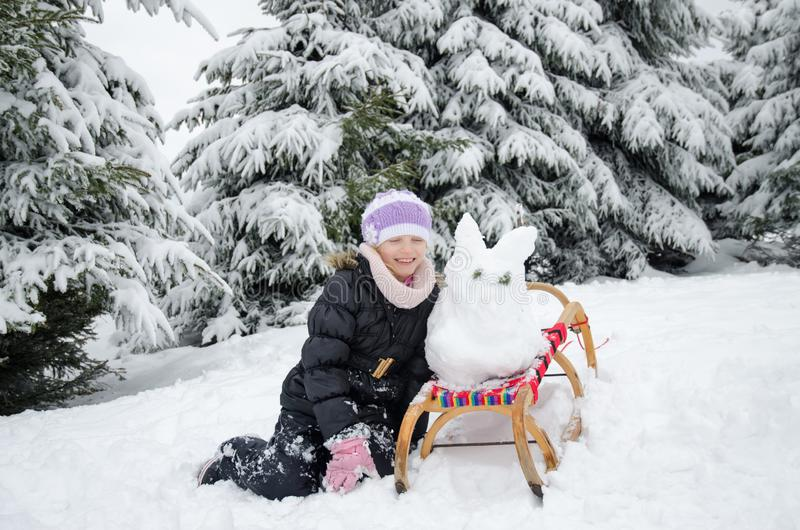 Child having happy winter time with lot of snow and little snowman built in sleight royalty free stock photography