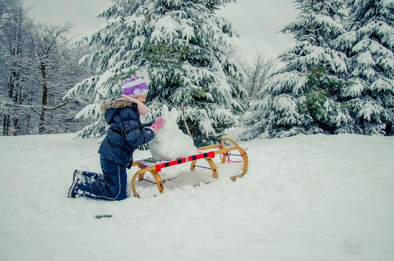 Child having happy winter time with lot of snow and little snowman built in sleight stock photos
