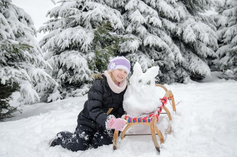 Child having happy winter time with lot of snow and little snowman built in sleight stock photo