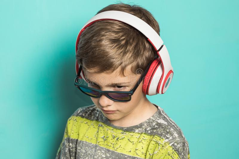 Child with headphones of music and funny expression royalty free stock image