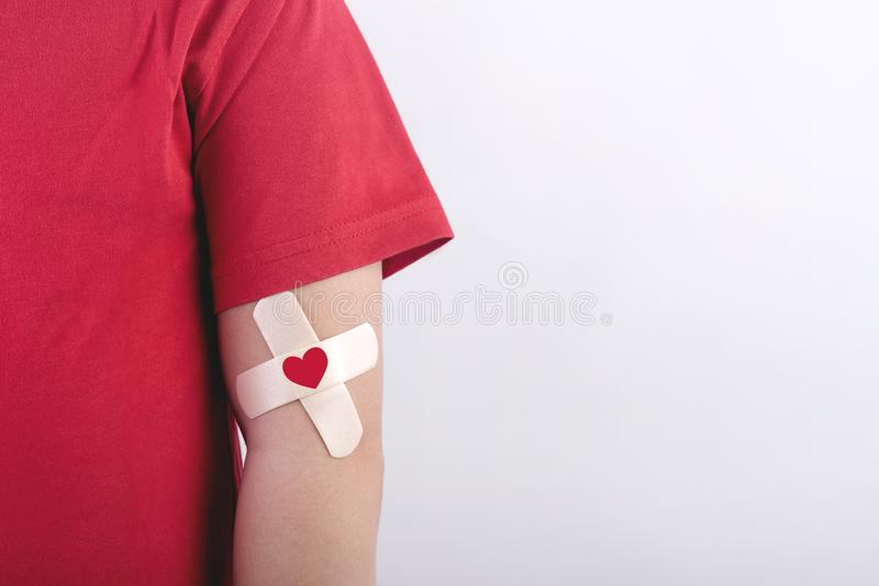 Child with a heart drawn on his arm. Blood donation concept. On white background royalty free stock photo