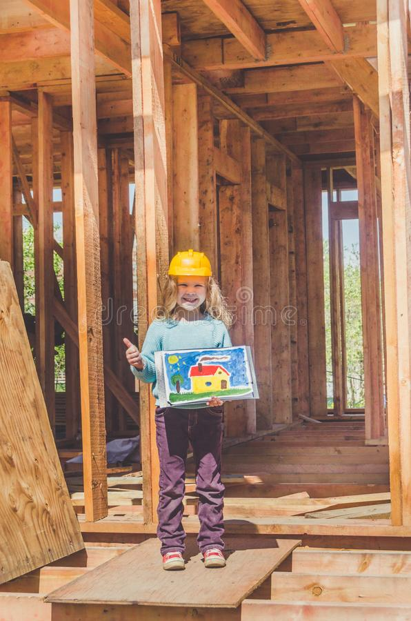 Child in a helmet on the construction site of a wooden house royalty free stock photo