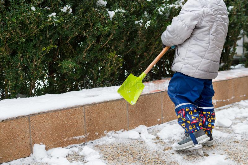 Child helping clearing snow from sidewalk. Candid authentic family winter activities. Snow shovelling. Child helping clearing snow from sidewalk. Candid stock photos