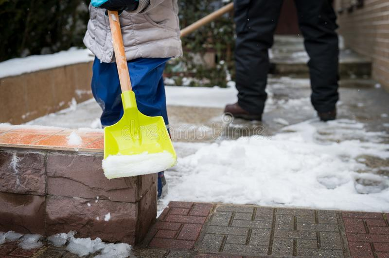 Child helping father clearing snow from sidewalk. Candid authentic family winter activities. Snow shovelling. Child helping father clearing snow from sidewalk stock photo