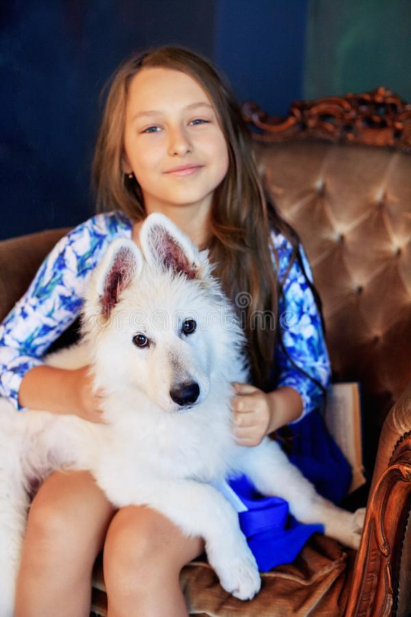 Child and her dog sitting in a chair. The concept of friendship stock photography