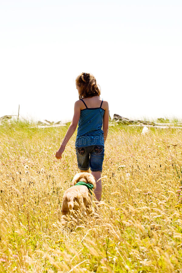 Download Child And Her Puppy Walking In A Field Of Grass Stock Image - Image: 20593833