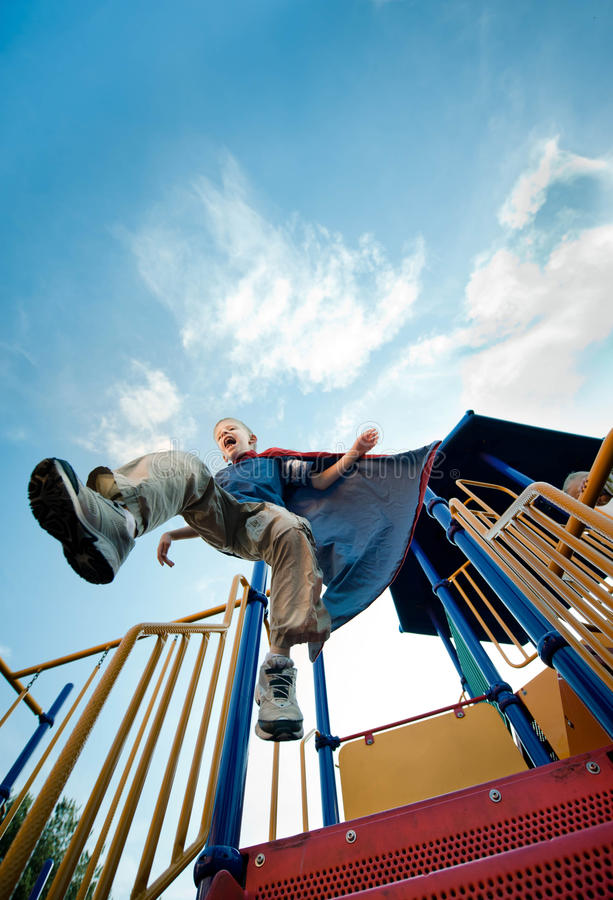 Child Hero. Super Boy! This child Super Hero to the rescue, protecting the playground. Jumping high and his cape. Fun way to show how boys use their imaginations royalty free stock photos