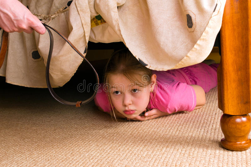 The child hides under a bed. Violence in a family. royalty free stock images