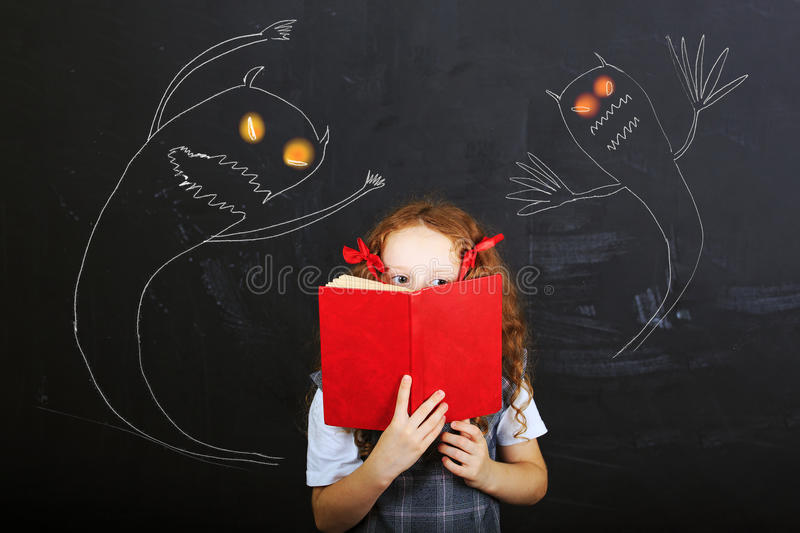 Child hiding behind the book, and is afraid near chalkboard. Education concept. stock images