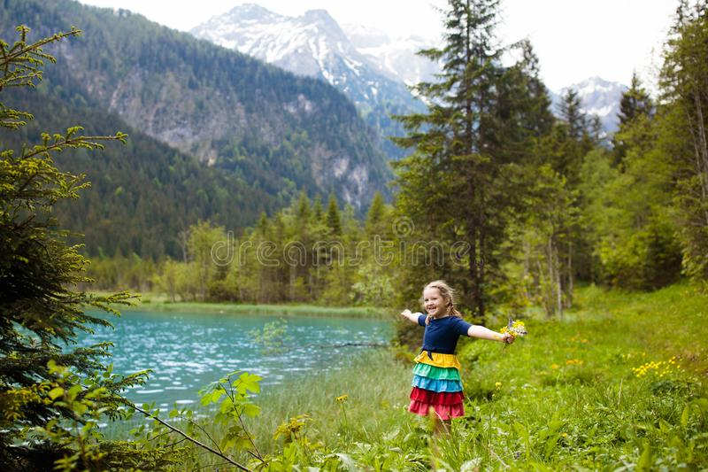 Child hiking in flower field at mountain lake royalty free stock photography