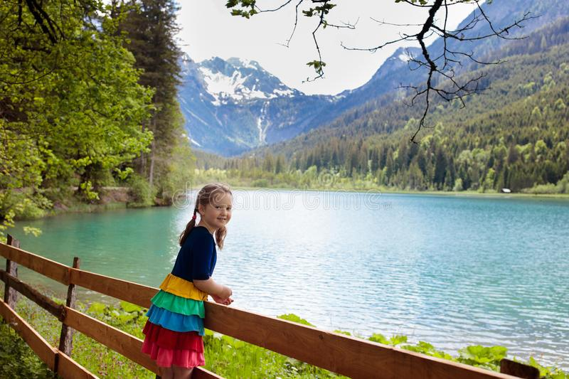 Child hiking in flower field at mountain lake stock photo
