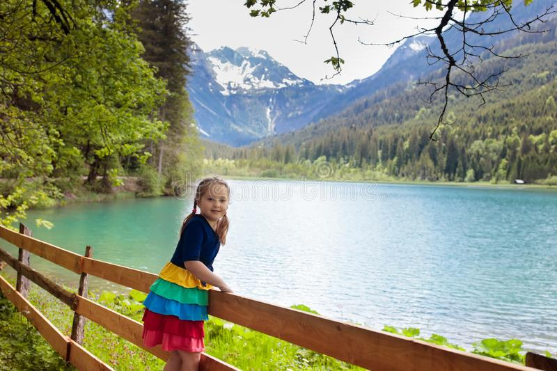 Child hiking in flower field at mountain lake royalty free stock image