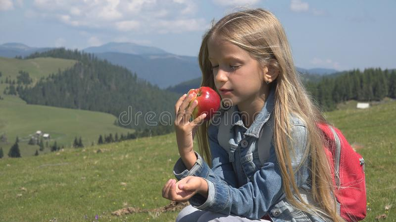 Child Hiking in Mountains, Kid Eating an Apple at Picnic, Little Girl at Camping stock photos