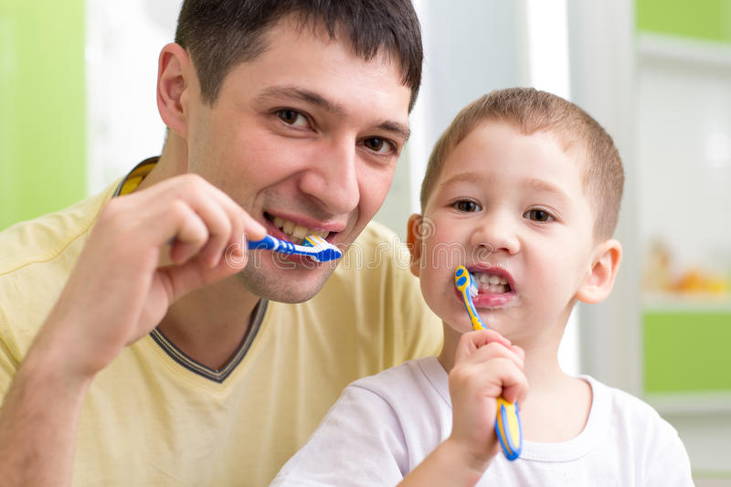 Child and his father brushing teeth in bathroom. Child boy and his father brushing teeth in bathroom royalty free stock image