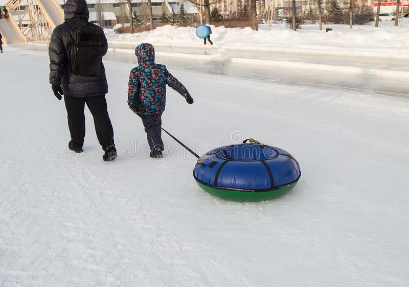 The child and his father are dragging a sledge tubing for skiing down the hill in the city Park in winter stock image