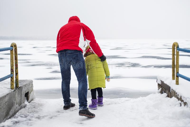 A child with his father walks in dangerous proximity to a frozen lake or river royalty free stock photo